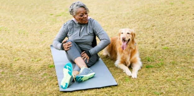 African American senior woman (60s) exercising in the park, sitting with her golden retriever.