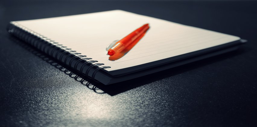 blank notebook and pen for freelance writing ideas