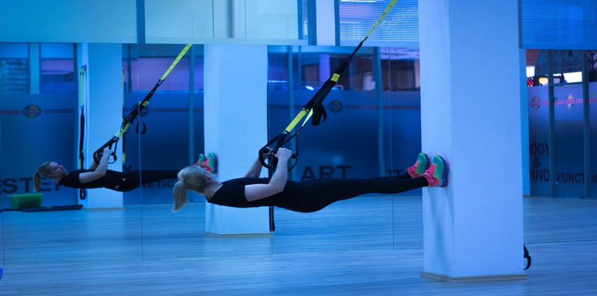 woman exercising with TRX bands