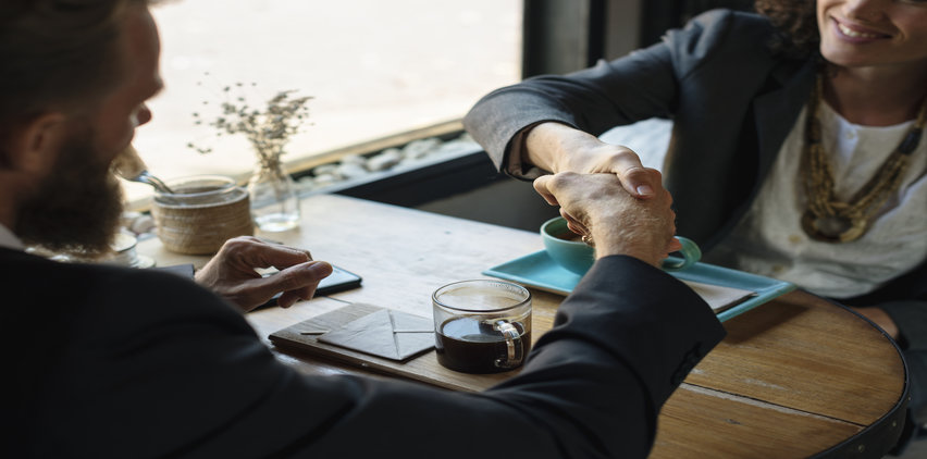 business handshake at coffee shop better paying freelance clients