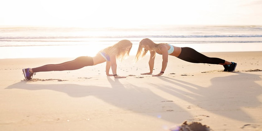 Pexels. Two women planking on the beach