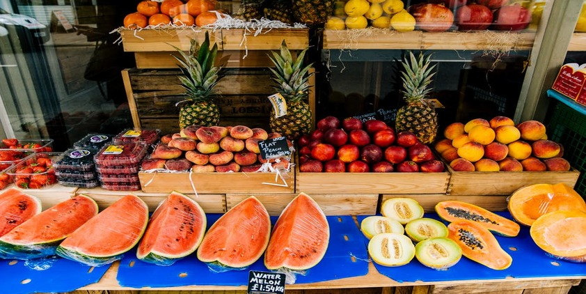 Pexels. Fruit stand including peaches, watermelon, pineapple, strawberries, and apples