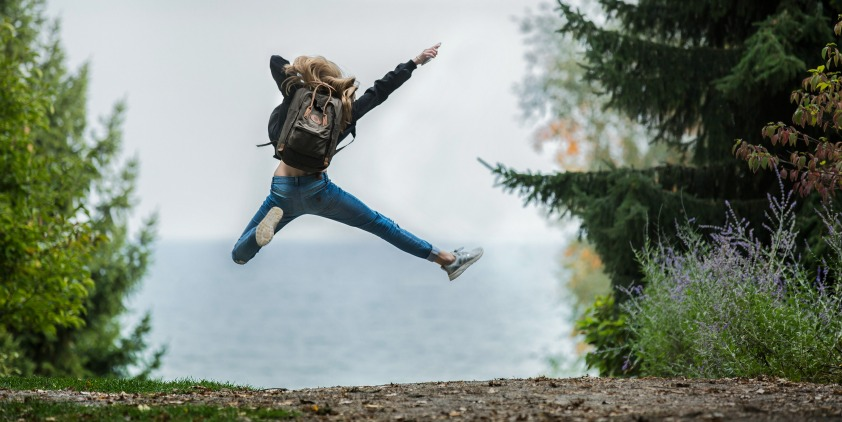 happy woman jumping after good night's sleep