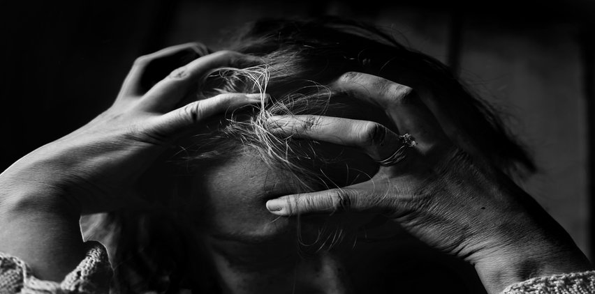 woman holding head in hands from stress