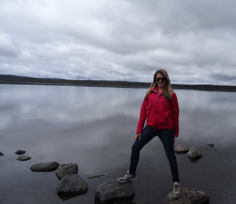 woman standing on rock in front of lake