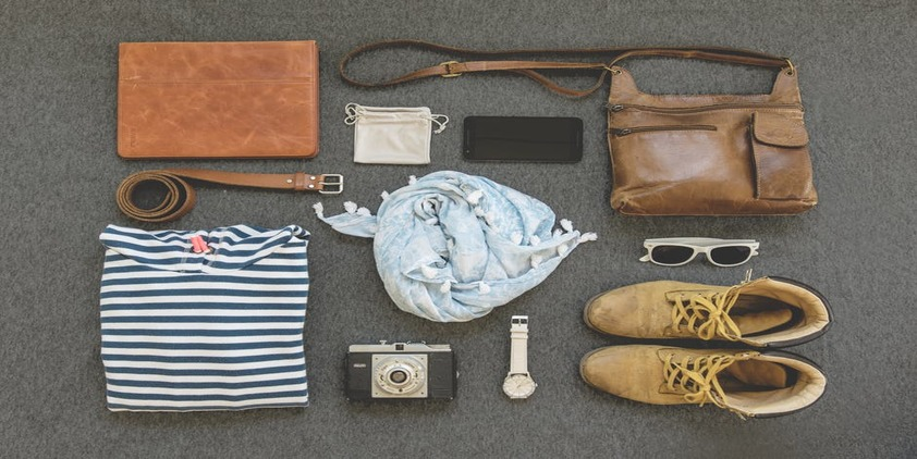Pexels. Shirt, Purse, Boots, Belt, Sunglasses, Watch, Cell Phone, Camera, and Scarf laid out on a table
