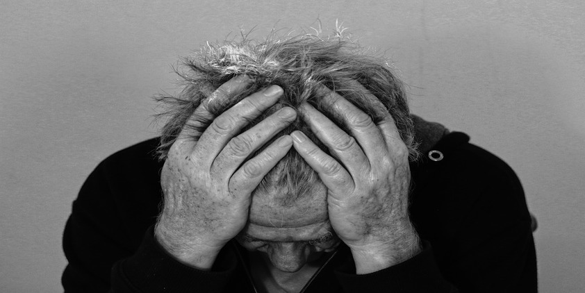 Pixabay. Older man in black and white holding his head