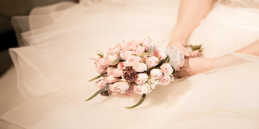 Pexels. Bride holding bouquet on her lap.