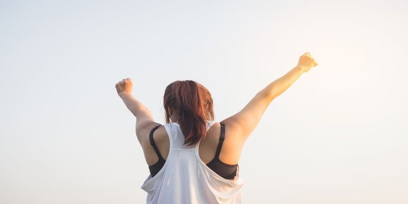 Pexels. Woman in work out tank and pony tail with her arms up in the air