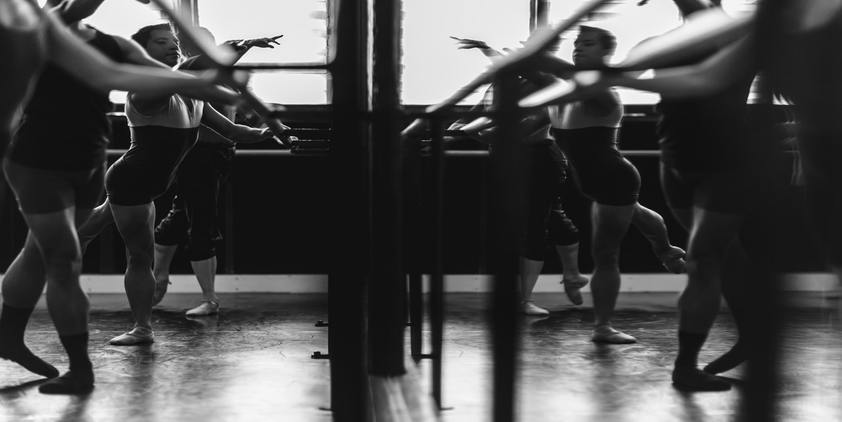 unsplash. Women dancing in front of mirror in black and white