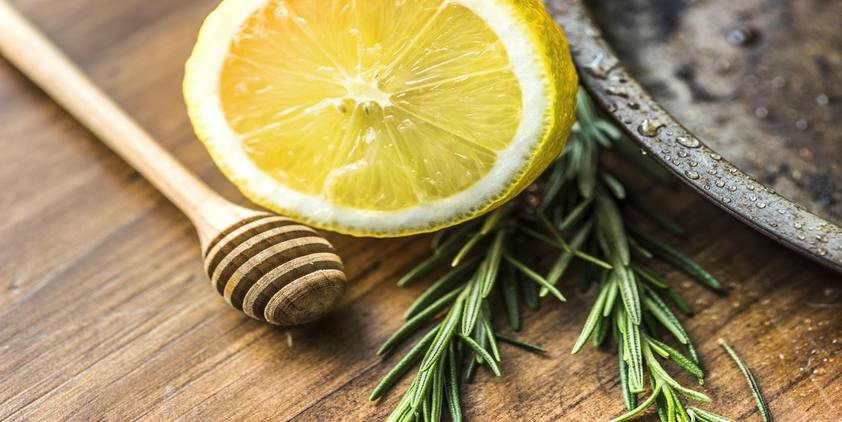 Unsplash. closeup of lemon and rosemary on a wooden table.