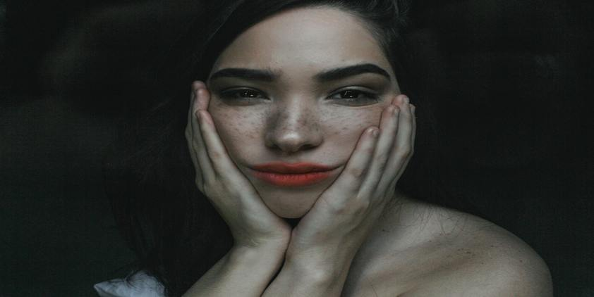 Unsplash freckled woman wearing red lipstick touching her face