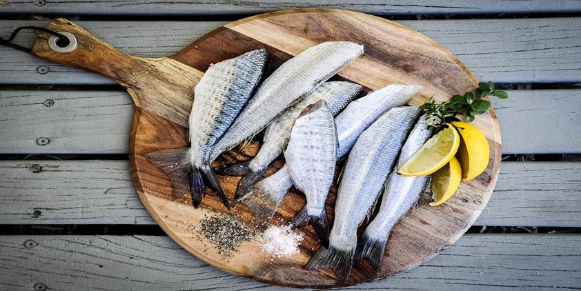 Unsplash. A bunch of fish on a circular wood board with pepper, salt, and lemon garnish