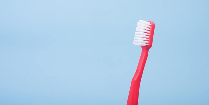 Unsplash Red toothbrush on blue background