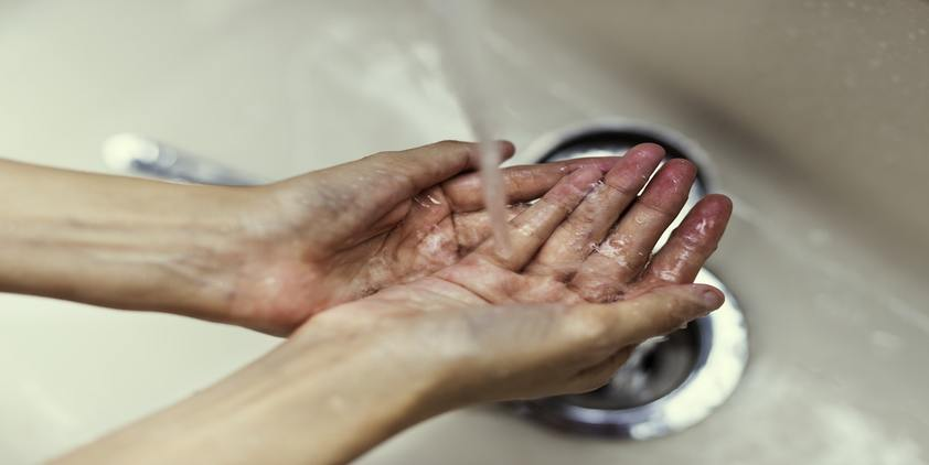 Unsplash. Person washing hands over sink