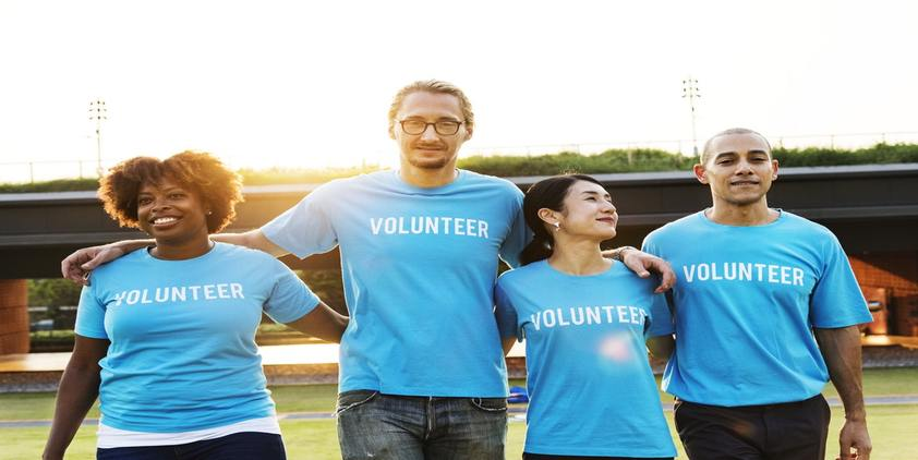 Unsplash. Women and men in blue volunteer shirts outside.