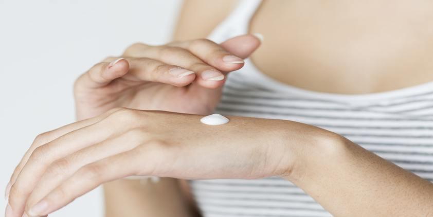 Unsplash. Woman in gray tank top rubbing cream into her hand