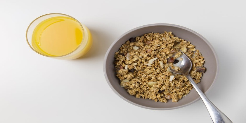 pixels. bowl of oatmeal with dried fruit and orange juice on white table