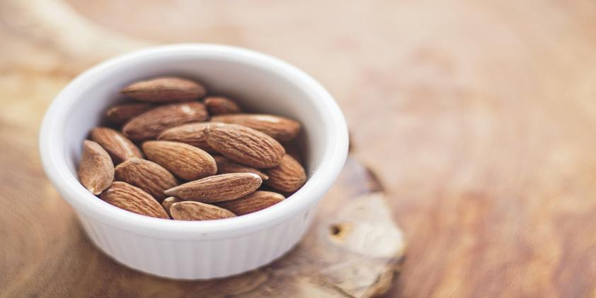 Unsplash. Small bowl of almonds on wooden counter