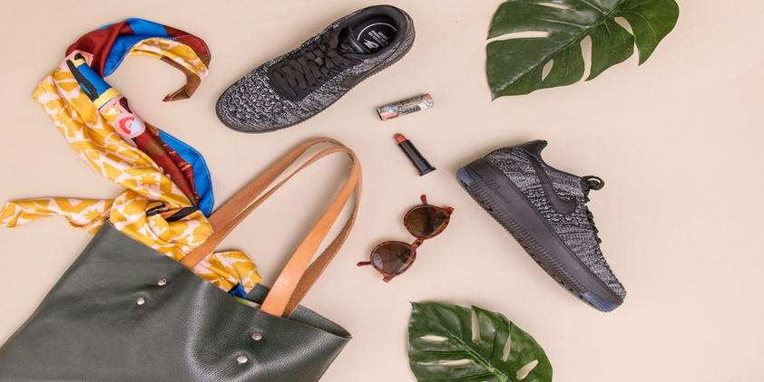 Unsplash. grey and brown bag with scarf, sunglasses, nike sneakers, and lip gloss on pink background with green leaves