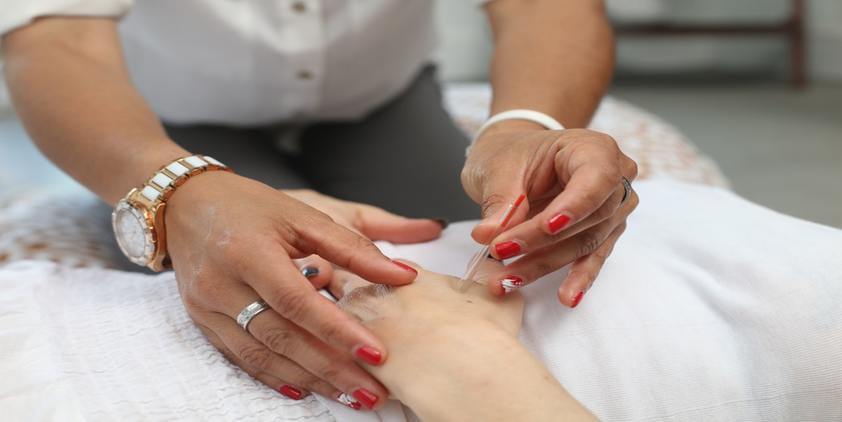 unsplash. woman with red nails and watch performing acupuncture on patient's hands