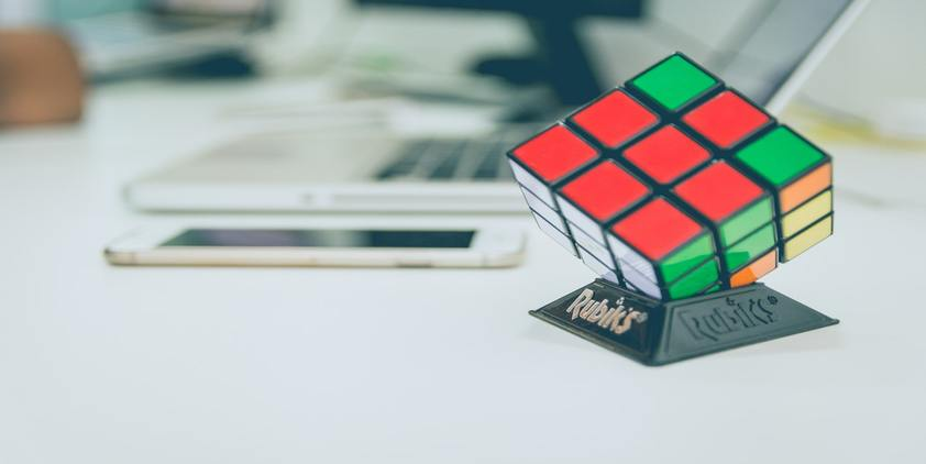 unsplash. rubiks cube on top of a white desk