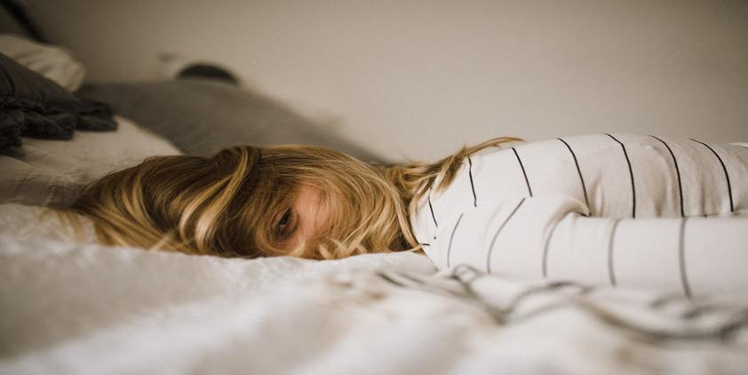 unsplash. blonde woman in white wearing white striped t shirt laying on bed