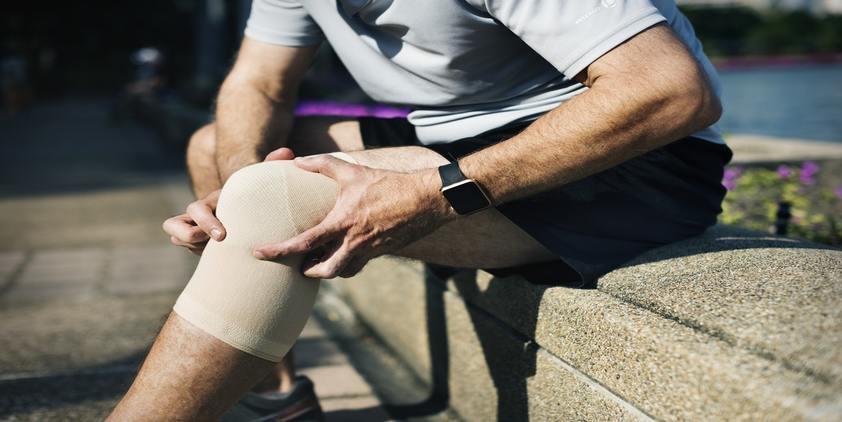 unsplash. man holding knee with brace on