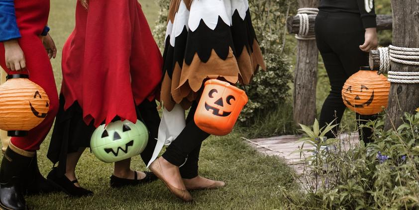 Unsplash. kids dressed up in costumes, going up front porch in halloween costumes with buckets