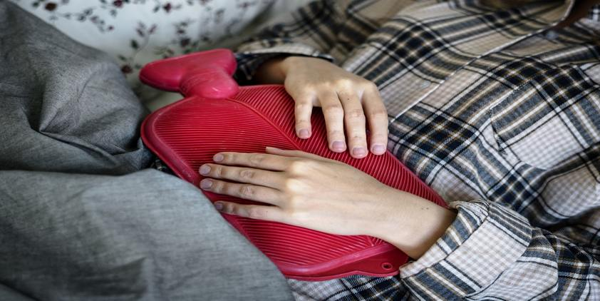 unsplash. woman in pajamas on couch holding red hot water bottle