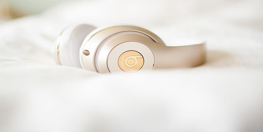 unsplash. beats by Dre headphones on white bed