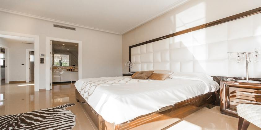 unsplash. brown wooden bed frame with white cover beside brown wooden nightstand