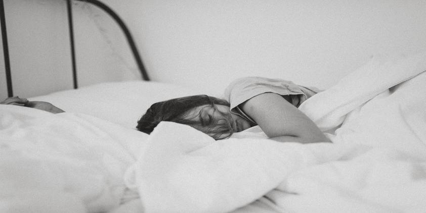 Unsplash. greyscale photo of woman laying in bed on her side