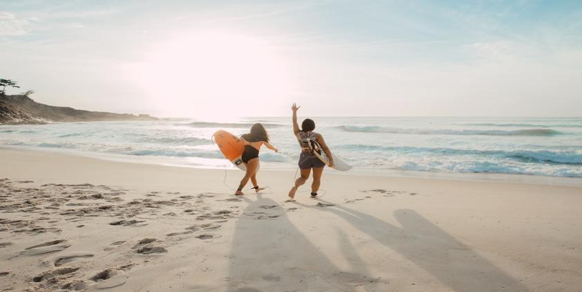 unsplash. two women on the beach with surfboards