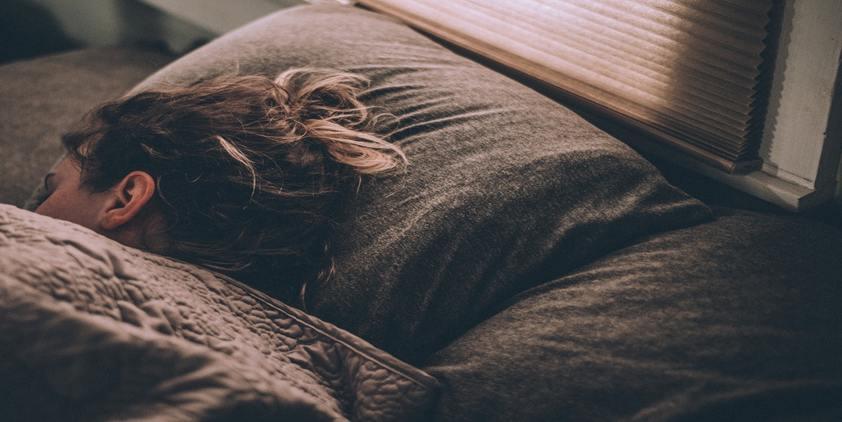 unsplash, woman sleeping under grey covers.
