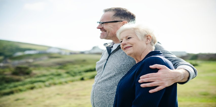 older adults hugging smiling outdoors
