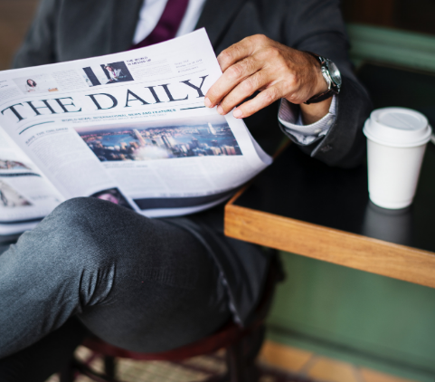 man sitting and reading newspaper