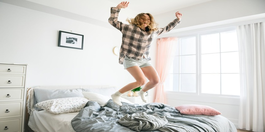 Pexels. Woman jumping on bed surrounded by pillows