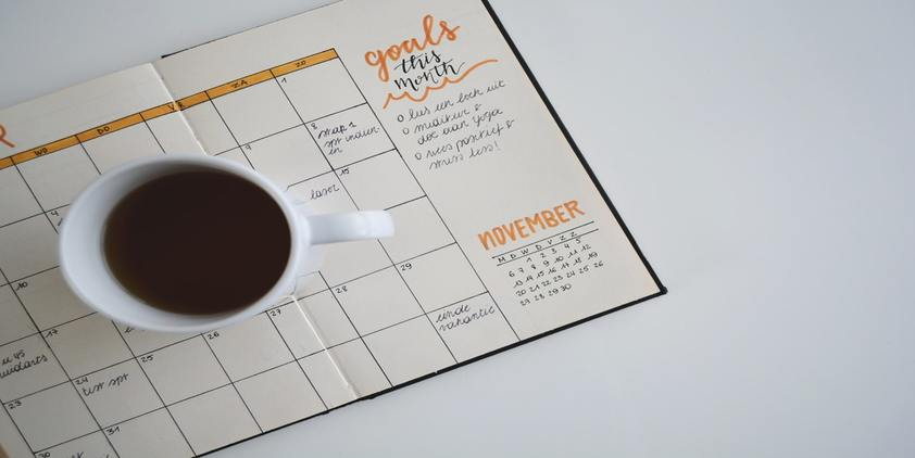 Unsplash. Handwritten calendar on notebook with orange highlights. Coffee cup in the middle.