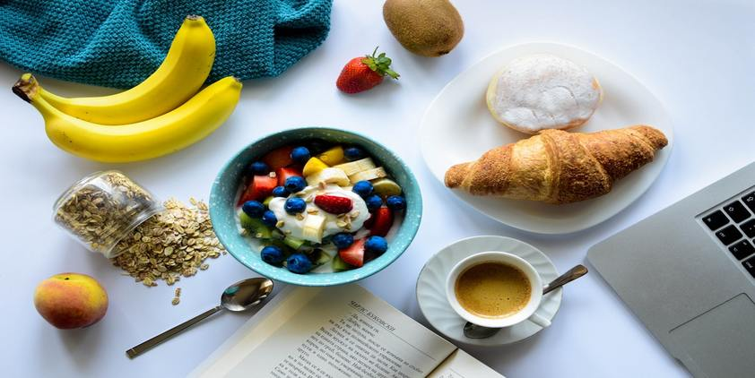 Unsplash. breakfast spread with fruit, oatmeal, coffee, and croissant