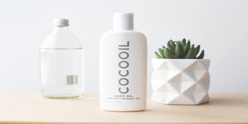 Unsplash. Coconut oil bottle and succulent on table