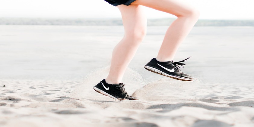 Unsplash. Woman running on beach in black sneakers