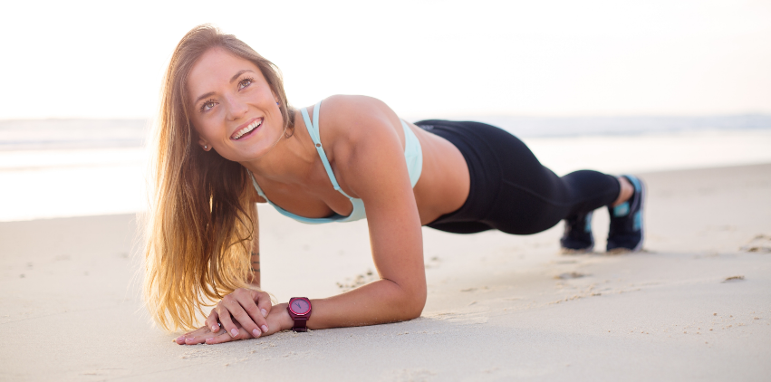 A woman smiles and does a plank exercise