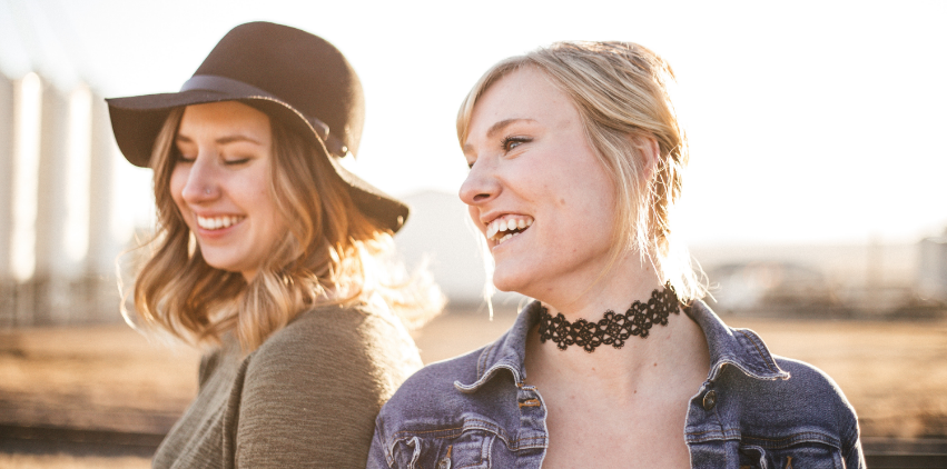 Two women smiling outside in the sunshine