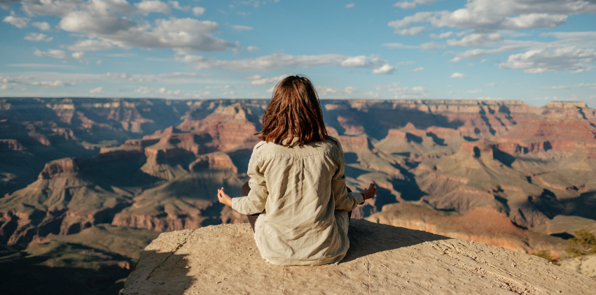 A woman meditates overlooking a canyon