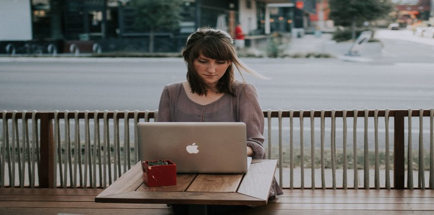 woman on laptop writing article pitch