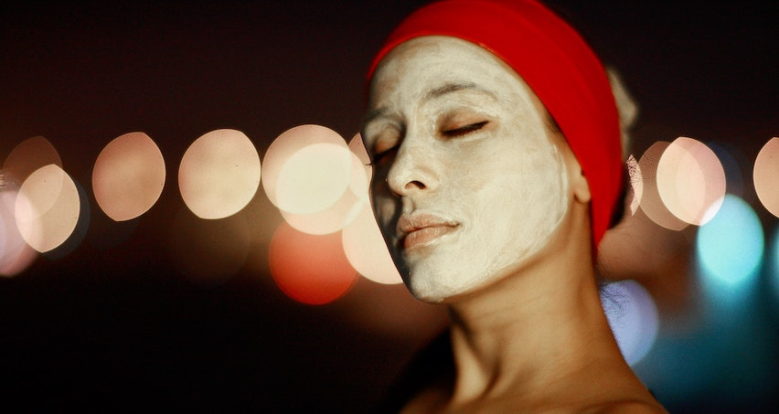 A woman cleans her skin with a face mask