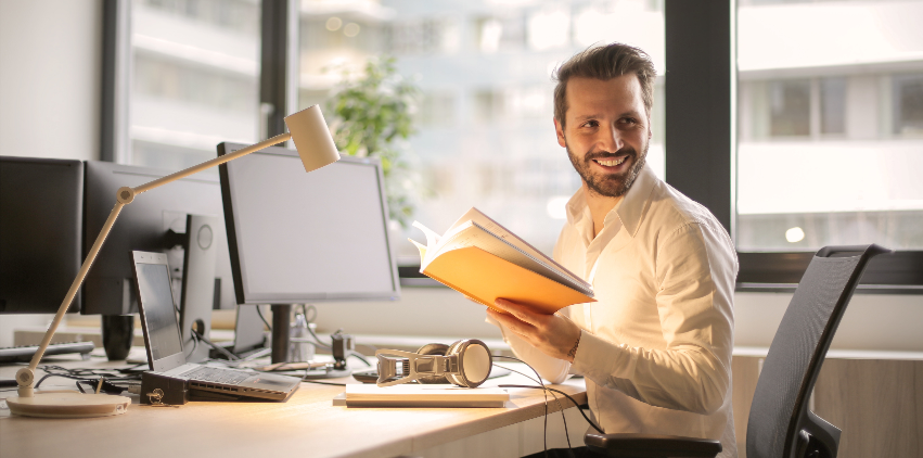 A man sits at his desk in his office and smiles while he works