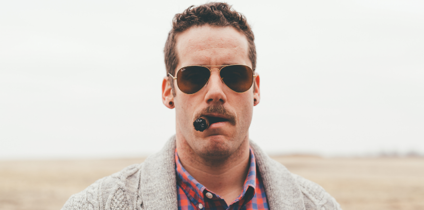 A man with a big mustache and sunglasses smoking a cigar