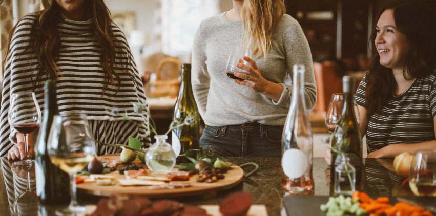 Women standing in a kitchen surrounded by wine and appetizers.